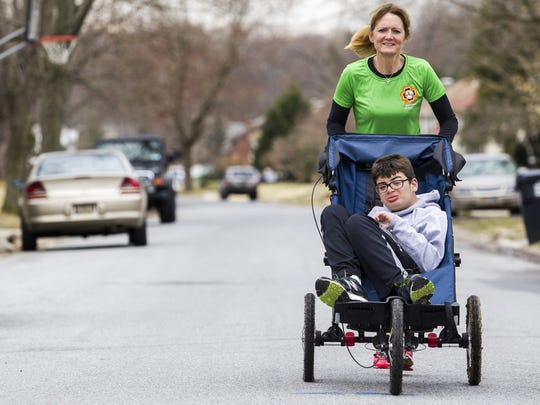 Deb Buenaga pushes her her son Preston near their home in Brandywine Hundred.