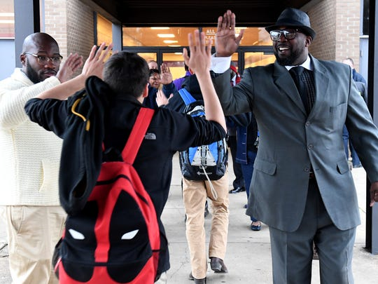 Shaheed Madyun and Pastor Undrae Johnson receive high-fives from a Haywood County High School student as he walked into school, Wednesday morning. Madyun and Johnson were joined with other parents and adults to show their support for the students after the student-lead protests, Monday and Tuesday.