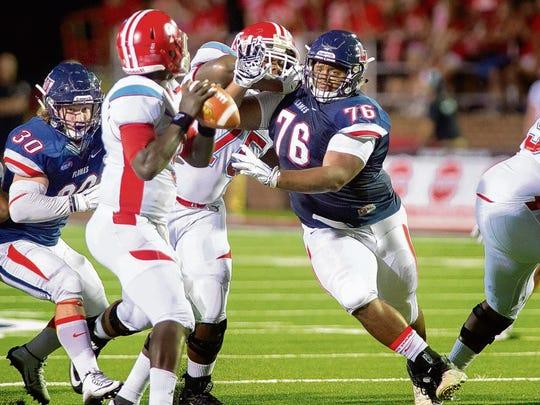 Delaware State quarterback Esayah Obado tries to avoid Liberty's JaRon Greene on Saturday.