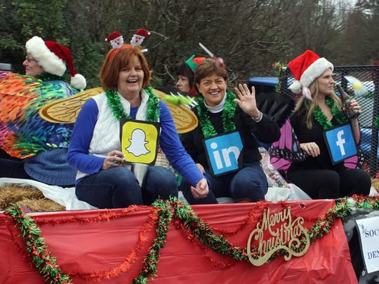 The Socialites of Denver, SC wave Sunday from their float in the Denver Downs Christmas Parade.