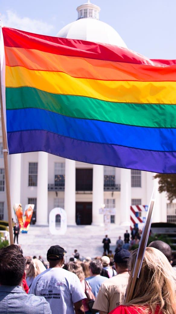 David Dineielli holds a rainbow flag during a rally