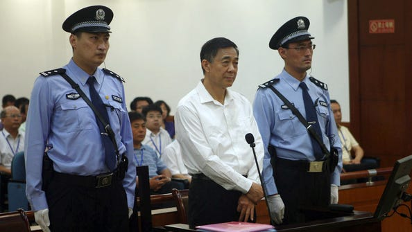 In this Aug. 22 photo released by the Jinan Intermediate People's Court, former Politburo member and Chongqing city party leader Bo Xilai, center, stands on trial at the court in eastern China's Shandong province.