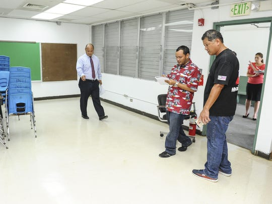 Guam Department of Education Superintendent Jon Fernandez, left, points out the need for another coat of wax on a classroom floor to Guam Cleaning Masters Human Resources and Senior Operations Manager E.J. Quintanilla, center, and GDOE Facilities and Maintenance Manager Billy Cruz  during an inspection tour at C.L. Taitano Elementary School in Sinajana on Tuesday, July 28.
