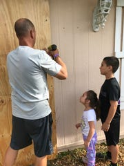 Mark Tesar removes plywood from the front door of his Golden Gate Estates home, as his daughter Dakota, 5, and Wyatt, 11, look on Monday morning.