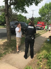 Eric R. Hable, a resident of an apartment building on fire in Wausau, tells a police officer how he tried to catch a woman who jumped from a third-floor window.
