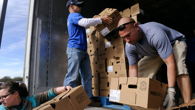 """Kayla Bailey (left), Dale Fogle and Gabriel Aparicio unload frozen turkeys from the back of an 18-wheeler Saturday at VFW Post 6873. All three are Dyess Air Force Base airmen assisting with """"Operation Thank You."""" The event was organized by San Antonio Shoemakers and provided the ingredients for making a Thanksgiving turkey dinner to qualified military families."""