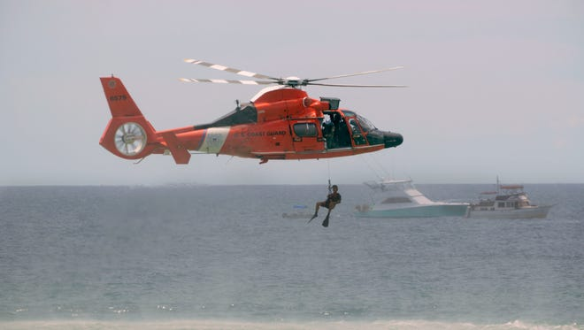 The Coast Guard does a simulated rescue during the Blue Angels Air Show Saturday, July 8, 2017 at Pensacola Beach.