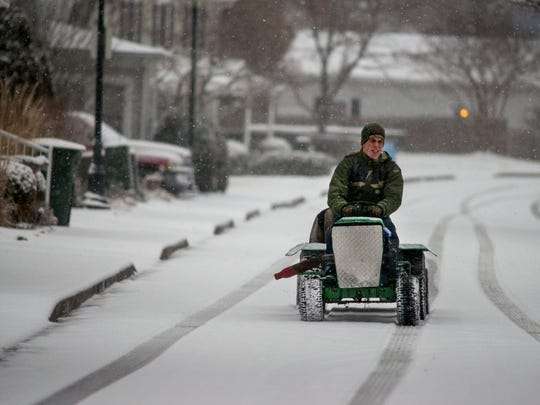 Caleb Bourne drives his modified lawn tractor along Powellton Avenue in Berlin on Thursday evening as snow falls.