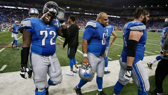 (From left) Lions offensive linemen Laken Tomlinson, Manny Ramirez and Travis Swanson walk off the field late in the fourth quarter of Sunday's loss at Ford Field.