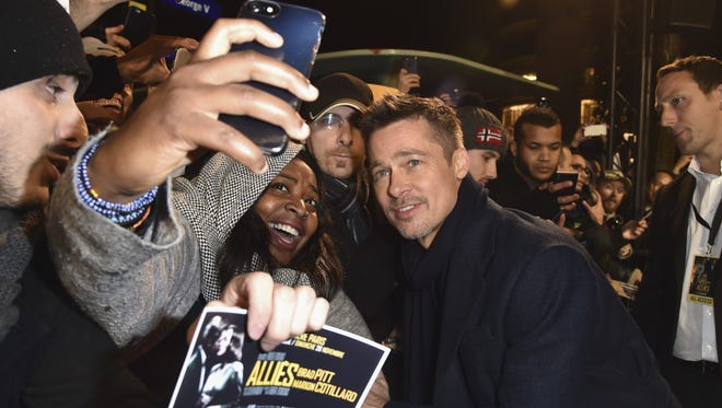 Brad Pitt takes a selfie with a fan at the Paris premiere of 'Allied' on Nov. 19.