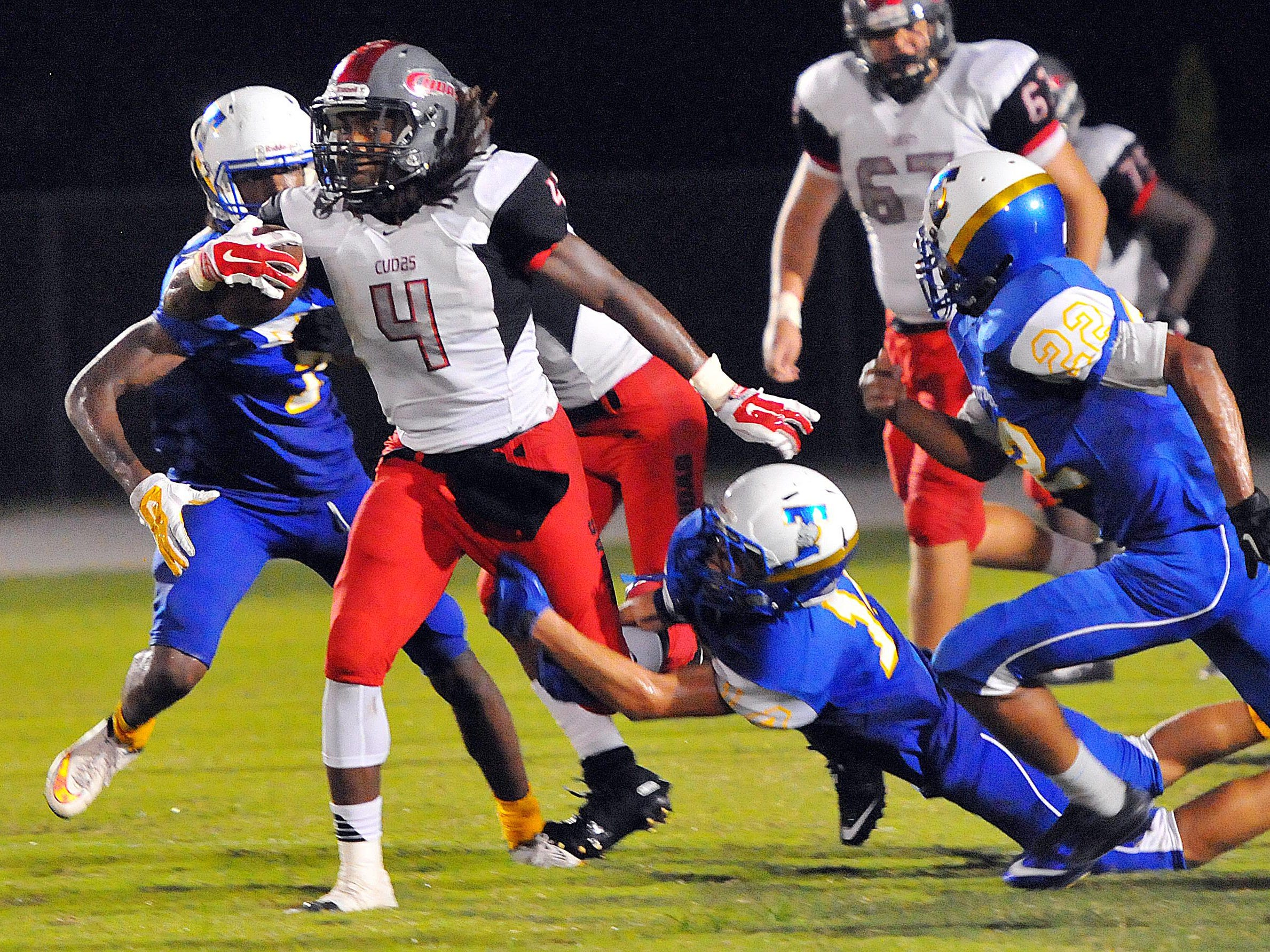 New Smyrna's Darrynton Evens picks up some hard-earned yards surrounded by a host of Titusville High defenders during Friday night's game at the Titusville High School.