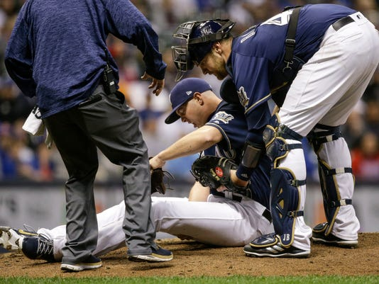 Milwaukee Brewers' Corey Knebel grabs his leg after falling to the mound while pitching to a Chicago Cubs batter during the ninth inning of a baseball game Thursday, April 5, 2018, in Milwaukee. (AP Photo/Tom Lynn)