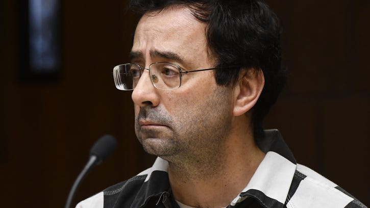 Dr. Larry Nassar listens as a young woman who was a former family friend speaks about alleged abuse by Nassar in court.