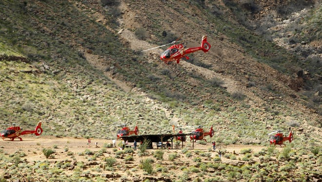 A Grand Canyon Helicopter flies in the western part of Grand Canyon National Park as others sit on landing pad on the Hualapai Reservation. Some 300-400 helicopters fly the area each day.