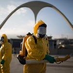 In this Jan. 26, 2016 file photo, a health worker stands in the Sambadrome spraying insecticide to combat the Aedes aegypti mosquito that transmits the Zika virus in Rio de Janeiro.