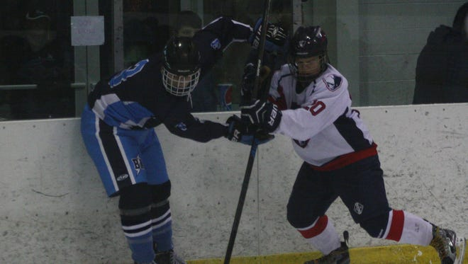 Livonia Franklin sophomore Nic Anderson (right) battles a Bay Area Thunder player for the puck during Wednesday's season-opening victory at Eddie Edgar Arena.