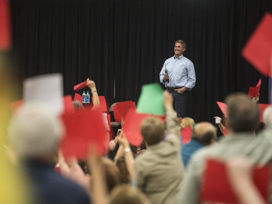 Sen. Jeff Flake smiles as the crowd boos and puts up red pieces of paper during a town hall at the Mesa Convention Center on April 13, 2017.