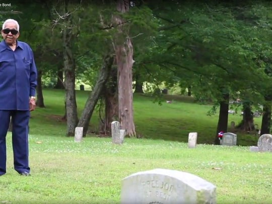 Charles Morris stands at the unmarked grave of his