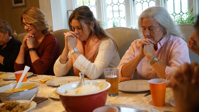 (left to right)Resident of the Limen House Barbara Adriance, Jessica Okonciewski and Stasia Fitzgerald say a pray before eating Thanksgiving dinner with fellow residents and alumni on Thursday.