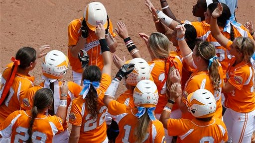 Tennessee's Megan Geer, top, is greeted by teammates at home plate after hitting a home run in the fourth inning against Florida in the NCAA Women's College World Series on Thursday in Oklahoma City. Geer's homer was the Lady Vols' lone hit in their 7-2 loss to Florida.