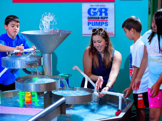Parents and children play in the water table section of the Little Buckeye Children's Museum.