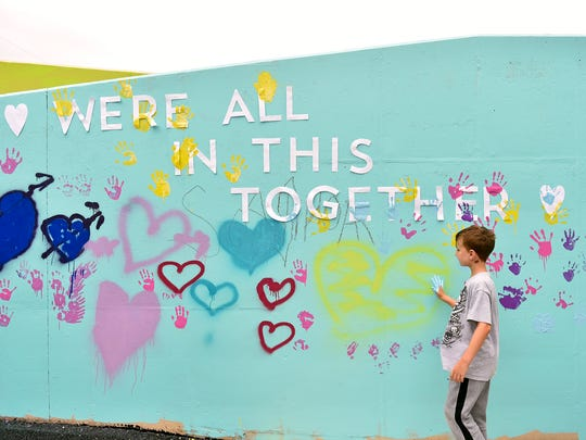 Dylan Lee, 8 of York Township, looks for a place to press his paint-covered handprint during the Penn Street Art Bridge Launch Party on the north side of the North Penn Street bridge near Smyser Street Saturday, July 29, 2017, in York. UpCollective York and York Time Bank collaborated to turn the bridge, which has long been a target of graffiti, into a public art space that anyone can transform with paint.
