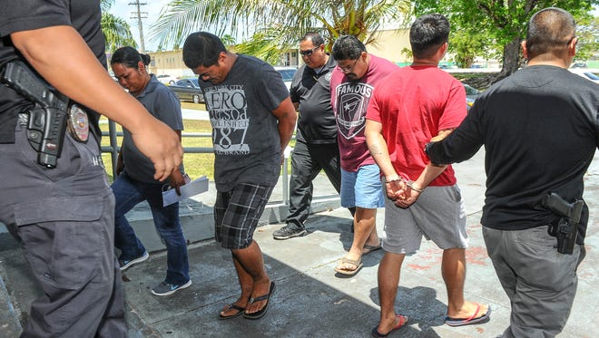Guam Police Department officers on Wednesday escort suspects arrested in connection to an alleged brawl at a cockpit shown in a recent viral video. They are Rodel Quenga Alforque, in checkered shorts, Rocindo Quenga Alforque, wearing glasses, and Liberty Joe Aguon Concepcion, in red shirt walking away.