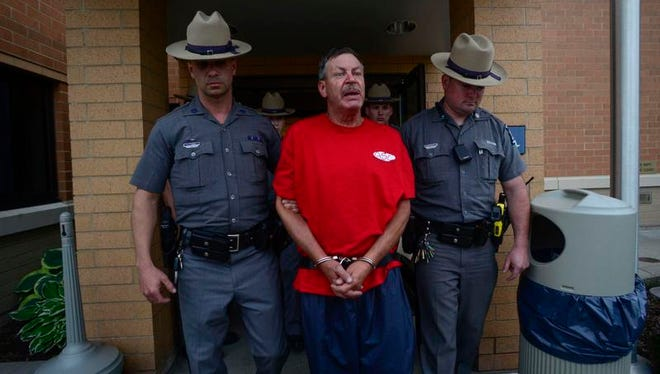 New York State Troopers escort Almond Upton after his May 2014 arraignment in Chenango Town Court.