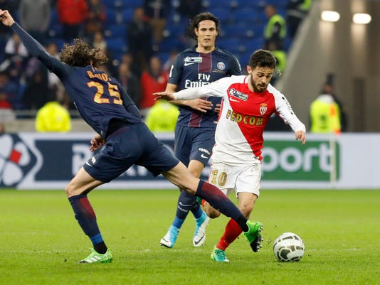 Monaco's Bernardo Silva, right, challenges for the ball with PSG's Roberto Edinson Cavani, left, during their League Cup final soccer match in Decines, near Lyon, central France, Saturday, April 1, 2017. (AP Photo/Laurent Cipriani)