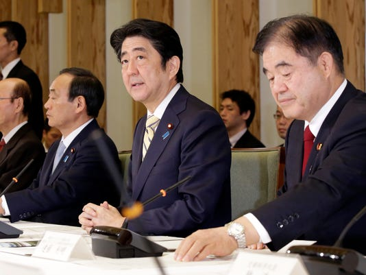 Japan's Prime Minister Shinzo Abe, second right, speaks during a meeting of Cabinet ministers on a new national stadium construction plan for the 2020 Tokyo Olympics at Abe's official residence in Tokyo Tuesday, Dec. 22, 2015. At right is Toshiaki Endo, minister in charge of the 2020 Tokyo Olympics.  Japan has selected a new design for the main stadium for the 2020 Tokyo Olympics after scrapping an earlier plan as too costly. Prime Minister Abe announced Tuesday that the winner is a design by renowned Japanese architect Kengo Kuma, construction company Taisei Corp. and Azusa design office. (AP Photo/Eugene Hoshiko, Pool)