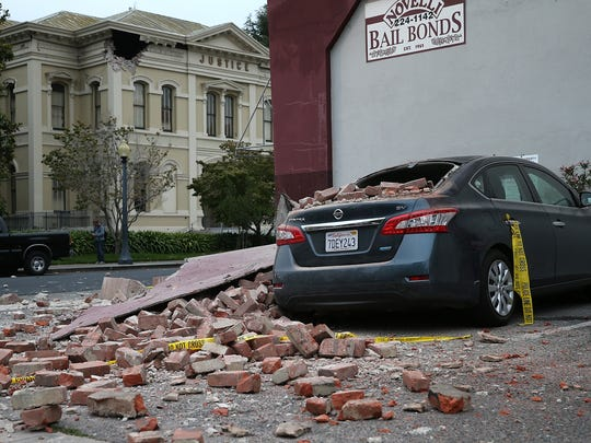 Bricks fell from a damaged building onto a car Sunday morning in Napa, Calif. In the background, the old Napa County Courthouse has a hole near the roofline. Near 200 suffered injuries in the quake.