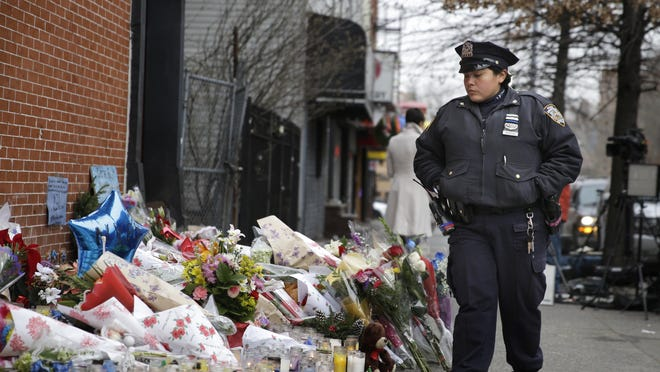 A New York City police officer looks over a makeshift memorial Monday, near the site where fellow officers Rafael Ramos and Wenjian Liu were slain in Brooklyn. Police say Ismaaiyl Brinsley ambushed the two officers in their patrol car in broad daylight Saturday, fatally shooting them before killing himself inside a subway station.