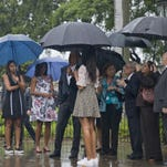 President Barack Obama, third from left, first lady Michelle Obama, second from left, and their daughters Sasha, left, and Malia, fourth from left, look at a statue of Cuban independence hero Carlos Manuel de Cespedes as they listen to City of Havana Historian Eusebio Leal, third from right, during their visit to Old Havana, Cuba, on Sunday.