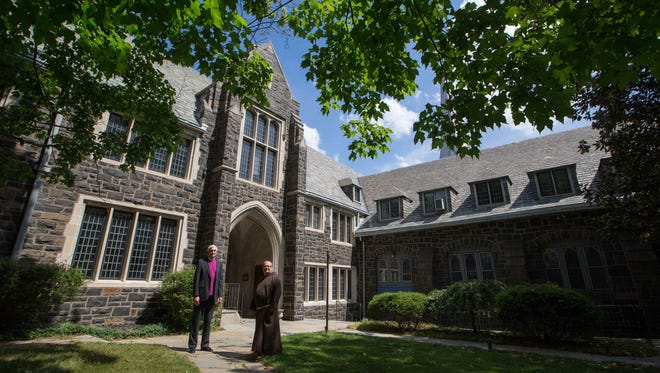 Brother Ronald Giannone, of the group Ministry of Caring, left, and the Rev. Wayne Wright, Episcopal bishop of Delaware, tour  Cathedral Church of St. John on May 26.  Giannone is converting the complex into housing for income seniors.
