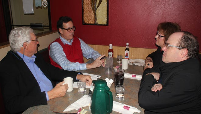 Ray Garringer (right), Williamsburg police chief and Iowa County supervisor, and his wife, Fonda (seated next to him) visit with Republican presidential candidate Rick Santorum (second from left), U.S. senator from Pennsylvania from 1995-2007, during Santorum's stop Tuesday, Jan. 26, at the Landmark Restaurant, Williamsburg.