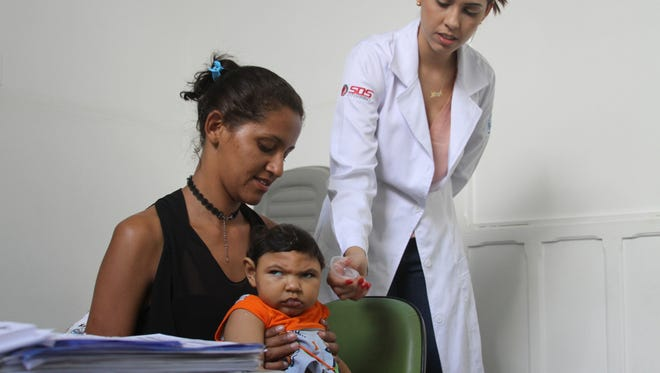 Miriam de Frana Araœjo with her son, Lucas Gabriel, during a routine checkup with an ear, nose and throat doctor in Campina Grande. Lucas, like many babies born with microcephaly, has auditory and vision problems.