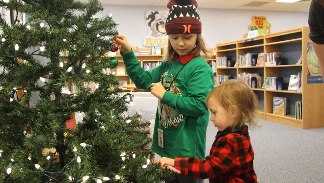 Adam Wallace (left) and his brother Lucian Wallace enjoy decorating a Christmas tree at Carlsbad Public Library on Tuesday.