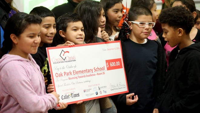 Fifth-grade students of Joan Karbowski hold a check given to her by the Corpus Christi Education Foundation on Thursday, Dec. 8, 2016, at Oak Park Elementary School in Corpus Christi.