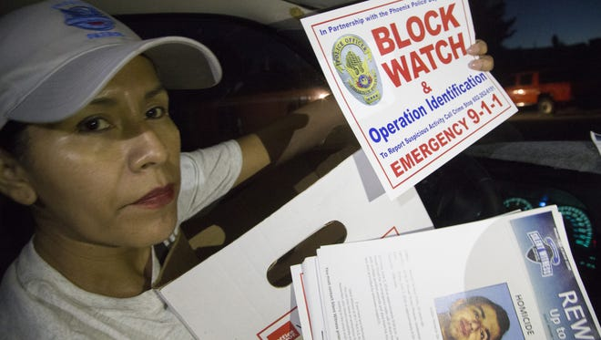 Rosa Pastrana holds up block watch fliers and posters about crimes committed in the area.