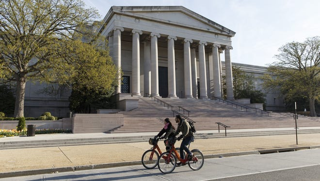 Cyclists ride past the National Museum of Art in Washington, Thursday, April 17, 2014.