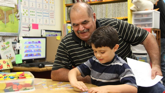 Rocky Jimenez works on a puzzle with his grandson, kindergartner John Davis Jimenez at K-3 Plus program's STEM Day on July 13, 2017. The CMS district invited parents to attend STEM Day and participate in various activities with the students.