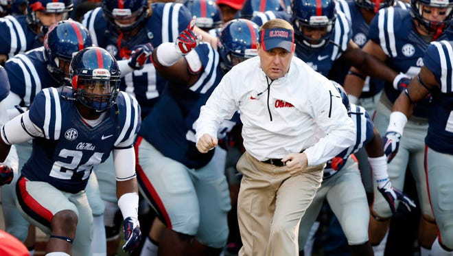 Hugh Freeze and his team runs onto the field prior to their game against Tennessee at an NCAA college football game in Oxford, Miss., Saturday, Oct. 18, 2014. (AP Photo/Rogelio V. Solis)