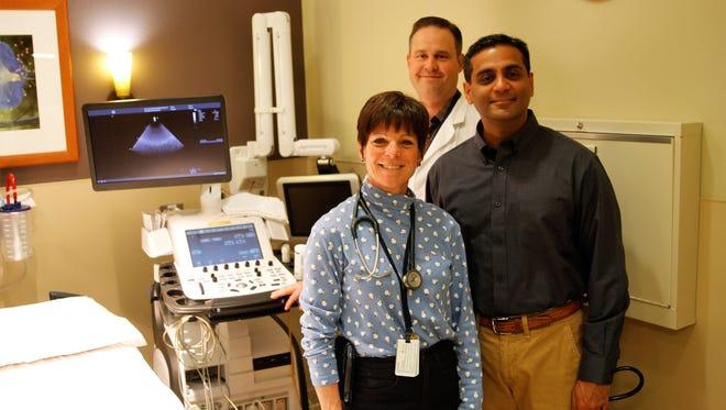 Physician Rachel Chaney, left, Jude Gabaldon and Sudhakar Girotra help provide free cardiac screenings for student athletes Saturday at the San Juan Regional Medical Center.