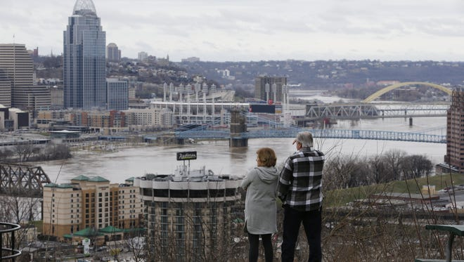 A couple looks at the flooded Ohio River from Devou Park in Covington on Saturday afternoon.