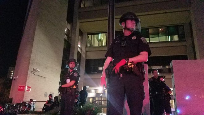 Austin police officers line in front of the department's headquarters on East Seventh Street early Saturday as dozens of protesters gathered to denounce the death of George Floyd this week.