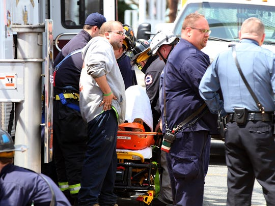 Emergency personnel treat a man who fell through a floor at a home under construction at Beach and Bath Avenues in Ocean Grove Thursday, April 13, 2017.