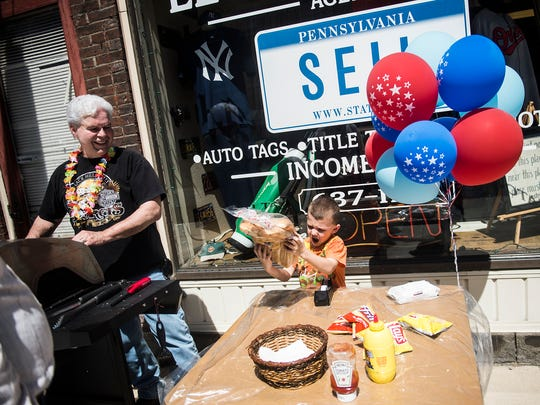 Braylen Johnson, 4, brings out a heavy bag of hot dog buns for volunteer David Morris, left, at the grill outside of the Lester J. Sell Agency on York Street on April 18, 2016.
