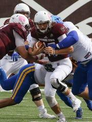 MSU quarterback Peyton Huslig pushes through the South