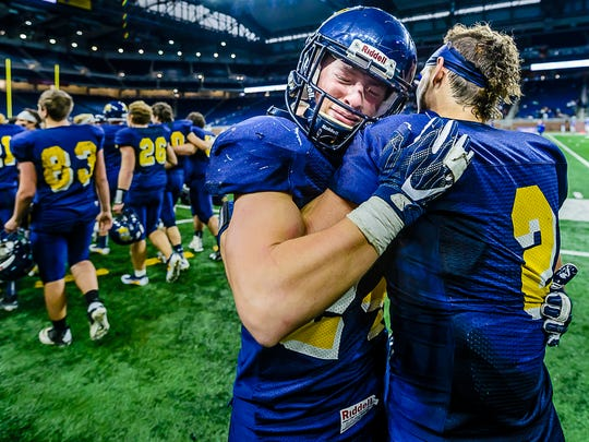 Pewamo-Westphalia senior tight-end Nathan Smith, left, hugs teammate Mason Schneider after their Division 7 state final win over Detroit Loyola Saturday November 26, 2016 at Ford Field in Detroit.