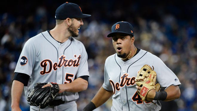 Tigers third baseman Jeimer Candelario is congratulated by relief pitcher Drew VerHagen (54) after starting a triple play during the sixth inning of the Tigers' 5-4 win on Friday, Sept. 8, 2017, in Toronto.
